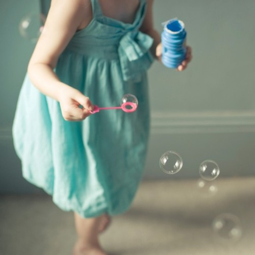 little girl playing with bubbles turquoise dress cute style